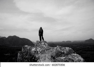 A woman standing on top of a limestone hill looking at the vast scenery in front. No face. Black and white.