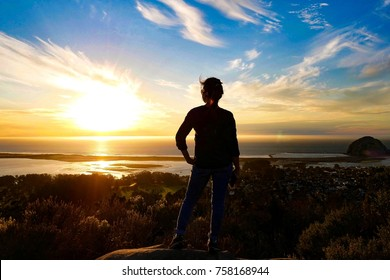 Woman was standing on the top of mountain watching beautiful view of sunrise and Morro Rock, California USA.