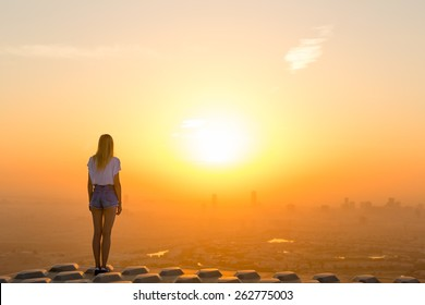 Woman standing on top of skyscraper overlooking the city at sunrise