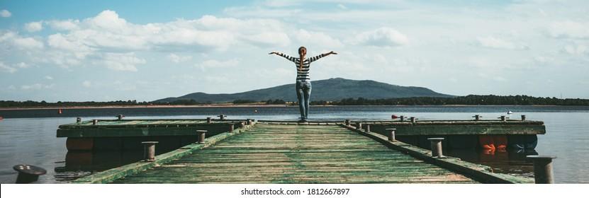 Frauen, die auf einem Holzsteg stehen und die Sonne mit den Armen genießen. Frauen auf einer Anlegestelle auf dem See grüßen die Sonne mit Armen weit offen. Authentisches Bild, kinematisches analoges Filmbild. Banner-Breitformat.