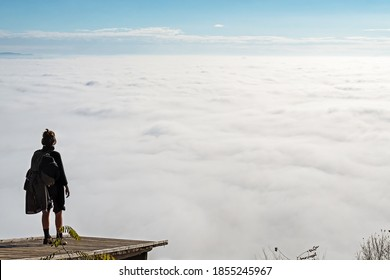 Woman standing on a wooden platform and enjoying the view of fog covered valley below. Hiking, achievement, expectation, optimism and self-reflection concepts.