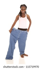 a woman standing in one leg of her pants with a smile on her face.
