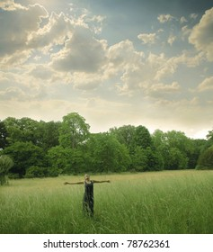 Woman standing with open arms on a green meadow