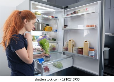 Woman standing at the open refrigerator with fruits, vegetables and healthy food