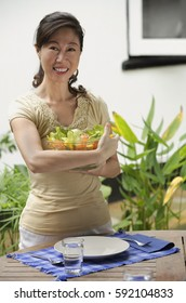 Woman standing at outdoor table, holding bowl of salad
