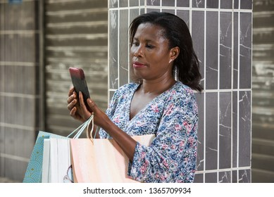 Woman standing outside against a wall and using a mobile phone to shop online. Portrait of woman holding shopping bags.