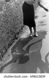 Woman standing in puddle on pavement