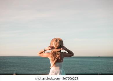 Woman standing at railing watching ocean