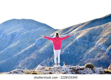 Woman standing with raised wide open arms and enjoying view of beautiful mountains