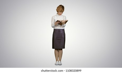 Woman standing and reading book on white background