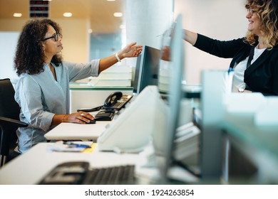 Woman standing at reception desk giving her card to the receptionist. Woman visiting municipality office being assisted by the administrator at front desk. - Shutterstock ID 1924263854