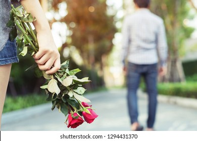 Woman Standing with a Red Rose on Hand Sadness Love in Ending Break up of Relationship Blurred Man Back Side Walking away parting  in public park outdoor.  Broken Heart in Valentine day Concept.