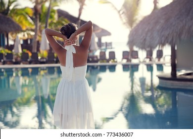 Woman standing at resort near luxury pool. Travel Holidays Vacation.