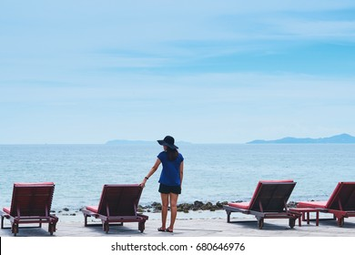 Woman standing at seaside near deck chair with blue sky and ocean background in her Summer Vacation