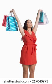 Woman standing with shopping bags on white background