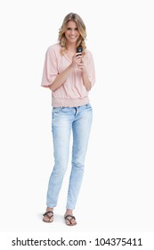 A woman is standing up smiling at the camera and holding a mobile phone against a white background