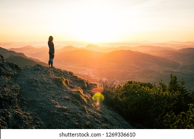 A woman standing at the top of the mountain and watching sunset over village of Terchova, Slovakia