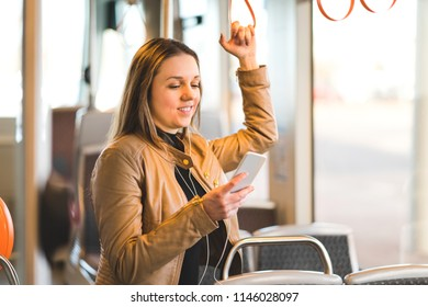 Woman standing in train, tram or bus holding the handle and using mobile phone. Happy female passenger texting with smartphone while riding in public transportation.