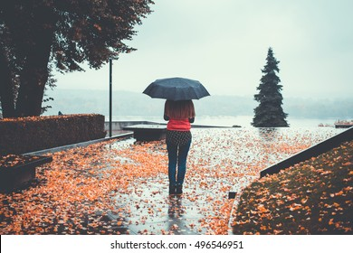 Woman standing with an umbrella on the road in the park in autumn rainy day