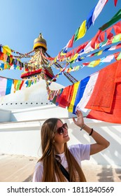 Woman standing under the colourful prayer flags with 'om mani padme hum' mantra written on them attached to the golden rooftop of The Bouddhanath Temple in Kathmandu, Nepal. She is smiling. Happiness