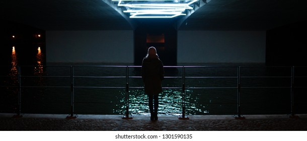 woman standing under a illuminated bridge
