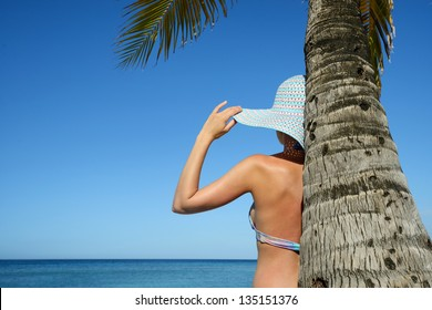 A woman standing under a palm tree watching the ocean.