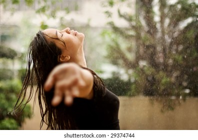 Woman standing under the rain, eyes closed and arms raised. Available space for text on the right side.