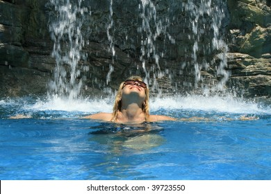 A woman standing under a waterfall in a swimming pool