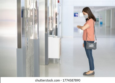 Woman standing and waiting for the elevator in the building, woman looking at her watch while waiting the elevator.