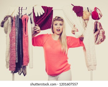 Woman standing in wardrobe with winter clothes, can not decide what to wear. Picking winter clothing concept.