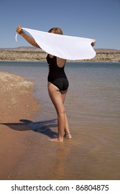 A woman standing in the water holding on to her white sarong