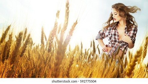 Woman standing in a wheat field; sunny summer day, lens flare