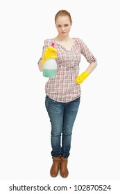 Woman standing while holding a spray bottle against white background