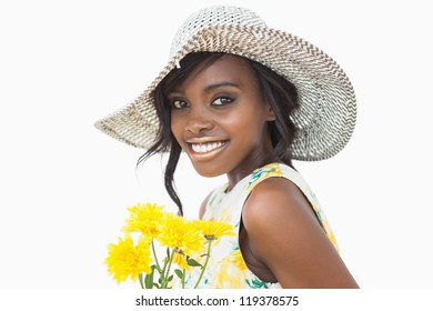 Woman standing while holding yellow flowers against white background