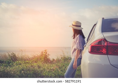 Woman standing with white car at sunset and beautiful view with vintage tone