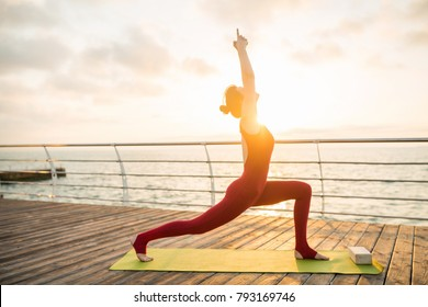 woman standing in yoga asana on sunrise by the sea, doing morning exercises on rug, slim healthy body, stretching