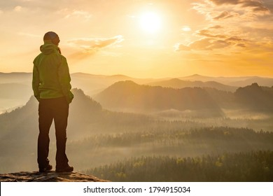 Die Frau steht allein auf dem Gipfel des Felsens. Wanderer beobachtet die Herbstsonne am Horizont. Schöner Moment das Wunder der Natur. Farbiger Nebel im Tal. Man wandert. Seidenstand