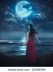A woman stands before the ocean and looks up to the bright moon.