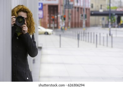 A woman stands behind a building and secretly takes photos