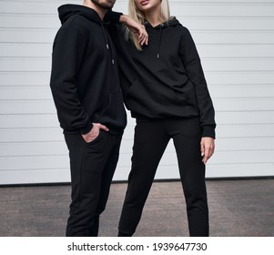 Woman stands in black no logo hoodie with bearded man behind her. Clothes branding mockup. Design template for casual sportswear