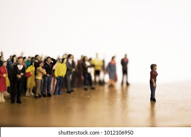 Woman stands in front of crowd or mob. Large group of people vs. one individual.  There are leaders and followers. One against many. Stand apart from the crowd.