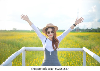 woman stands happily in the flower garden. sunhemp