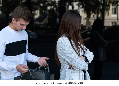 Woman stands with her back to man with shopping bags. Girl offended by the guy while shopping. Lovers quarreled