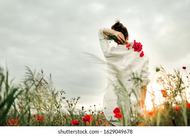 Woman stands holding a poppies flower bouquet over a back, among the meadow