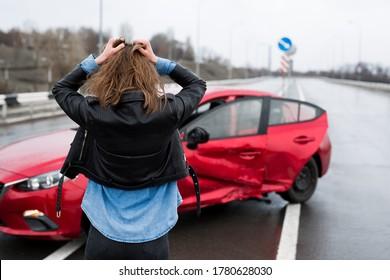 Die Frau steht nach einem Unfall in der Nähe eines kaputten Autos. Hilferuf. Kfz-Versicherung