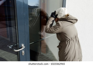 Woman stands near a door and looks in through the window, reflection