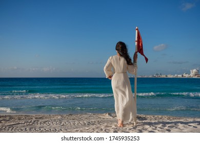 A woman stands on the beach near the red flag.