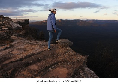 Woman stands on a cliff and looks at the landscape from Lincoln Rock Lookout at sunrise in the Blue Mountains National Park in the Blue Mountains region of New South Wales, Australia