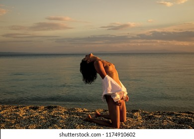 Woman stands on knees on beach in evening. Girl sexy, topless, naked breasts with wild hair at seashore at sunset. Erotic concept. Attractive young lady suntanning nude, nudist, enjoy last sun rays