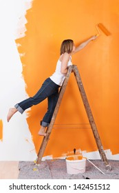 Woman stands on a ladder to paint her walls orange